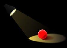 Le projecteur illumine la boule en verre rouge Photographie stock libre de droits
