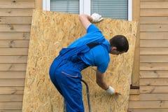 Le propriétaire de la maison enlève la protection contre la fenêtre après une catastrophe photo stock