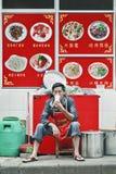 Le propriétaire de restaurant chinois fait une pause dehors, Kunming, Chine image stock