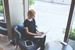 Le propriétaire de restaurant féminin blond emploie le filet-livre portatif pendant le jour de travail Photographie stock libre de droits