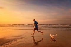 Le propriétaire et le chien courent à la plage dans le temps de coucher du soleil Photo stock