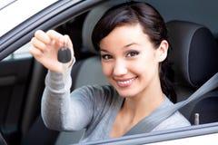 Le propriétaire heureux d'une nouvelle voiture montre la clé de voiture photos stock