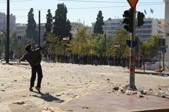 Le protestataire projette la roche contre d'autres protestataires Photographie stock libre de droits
