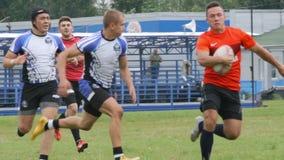 Le protezioni di rugby trattengono un giocatore su un campo video d archivio