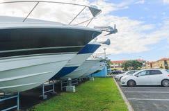 Le prue delle barche che attaccano dallo scaffale per la conservazione del supporto davanti alle automobili Immagini Stock