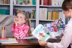 Le psychologue d'enfant discute dessiner une petite fille Image stock