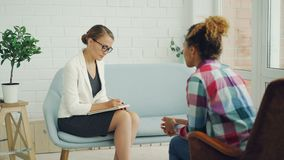Le psychologue professionnel écoute la patiente préoccupée de fille d'Afro-américain et écrit dans le carnet tandis qu'elle clips vidéos