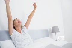 Le puits a reposé la femme blonde s'étirant dans le lit et le sourire photographie stock