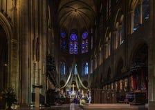 Le pupitre, l'autel et la croix du Notre Dame de Paris Cathedral avec les fenêtres en verre teinté le long du mur arrière dedans photos libres de droits