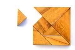 Le puzzle en bois de tangram dans l'attente carrée de forme accomplissent sur le blanc Photographie stock