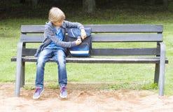 Le pysen som öppnar hans ryggsäck Barnsammanträde på en träbänk utomhus- Utbildning skolabegrepp Royaltyfria Foton