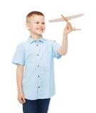 Le pysen som rymmer en träflygplanmodell Royaltyfri Foto