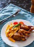 Le quaglie e le patate di Oasted sono servito in un piatto bianco fotografia stock