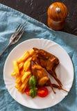 Le quaglie e le patate di Oasted sono servito in un piatto bianco immagini stock libere da diritti