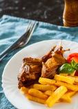Le quaglie e le patate di Oasted sono servito in un piatto bianco fotografie stock