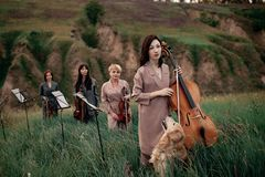 Le quartet musical femelle avec les violons et le violoncelle dispose à jouer au pré fleurissant Photos libres de droits