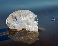 Le quartz clair a découpé l'étranger maya ovale Crystal Skull s'étendant sur le sable humide au lever de soleil photographie stock libre de droits