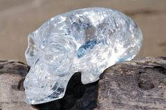 Le quartz clair a découpé l'étranger maya ovale Crystal Skull s'étendant sur le sable humide au lever de soleil images libres de droits