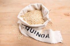 Le quinoa s'écaille dans un sac crème de tissu avec le label marqué au poncif Image libre de droits