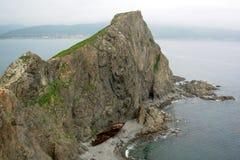 Le récipient a détruit près d'une roche de mer Image stock