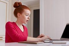 Le rédacteur doué femelle perplexe des travaux en ligne de question à distance à la maison, habillé en passant, a les cheveux rou photos stock