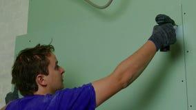 Le réparateur font pour installer la cloison sèche utilisant le tournevis et la vis banque de vidéos