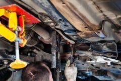 Le réparateur soude le silencieux sur la voiture par la soudure d'argon Photographie stock libre de droits