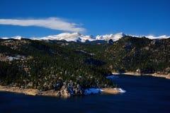 Le réservoir de montagne avec la neige a couvert des crêtes et des pins Image stock