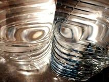 Le résumé forme l'eau en bouteille filtrant la lumière sur le gris, le bleu et le blanc Images libres de droits