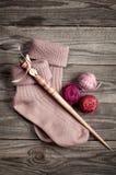 Le rétro axe en bois et le pourpre ont tricoté des chaussettes avec une boule de ya Photographie stock