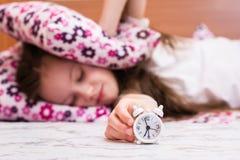 Le réveil blanc se tient sur la table sur le fond d'une fille couvrant ses oreilles d'oreillers photographie stock