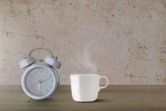 Le réveil classique bleu et la tasse de café blanc chaude avec la vapeur sur le vintage murent le fond Photos stock