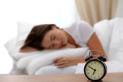 Le réveil se tenant sur la table de chevet a déjà sonné le début de la matinée pour réveiller la femme dans le lit dormant à l'ar Images libres de droits