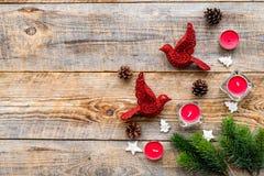 Le réveillon de Noël avec les branches impeccables, les jouets d'oiseau et les cônes de pin sur le fond en bois complètent la maq Photos stock