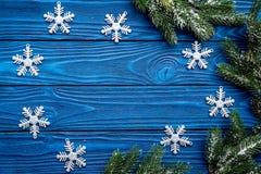 Le réveillon de Noël a placé avec les branches impeccables et les jouets de flocon de neige sur le fond en bois bleu complètent l Images libres de droits