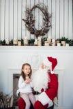 Le rêve est vrai dans le christmastime petite fille mignonne heureuse s'asseyant sur le recouvrement de Santa Claus et d'étreinte Photos stock