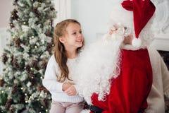 Le rêve est vrai dans le christmastime petite fille mignonne heureuse s'asseyant sur le recouvrement de Santa Claus et d'étreinte Image stock