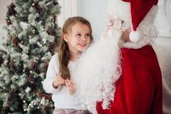 Le rêve est vrai dans le christmastime petite fille mignonne heureuse s'asseyant sur le recouvrement de Santa Claus et d'étreinte Image libre de droits
