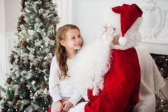 Le rêve est vrai dans le christmastime petite fille mignonne heureuse s'asseyant sur le recouvrement de Santa Claus et d'étreinte Photos libres de droits