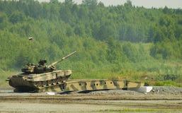 Le r?servoir T-80 conduit sur le pont induit par l'obstacle images stock