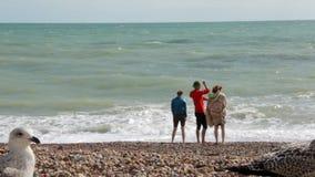 Le R-U, Brighton Deux filles et un type des vacances d'été se tenant sur la plage près de l'eau de l'Océan Atlantique Le type banque de vidéos