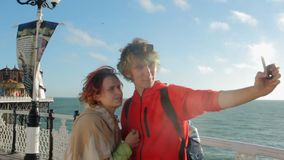 Le R-U, Brighton Les jeunes couples gais posent ensemble pour le selfie Amants heureux voyageant des vacances sur apprécier d'océ banque de vidéos