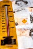 Le R-U dix notes et thermomètres de livre Photographie stock