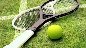 Le racchette e la pallina da tennis di tennis sono situate sul campo da tennis sull'erba Immagine Stock Libera da Diritti