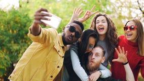 Le ragazze alla moda ed i tipi dei giovani stanno utilizzando lo smartphone per prendere il selfie in parco che posa per la macch immagini stock