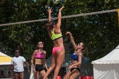 Le ragazze alla spiaggia volley nella città durante le vacanze estive Fotografia Stock