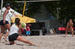 Le ragazze alla spiaggia volley nella città durante le vacanze estive Immagine Stock