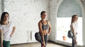 Le ragazze attraenti snelle stanno praticando le pose dell'equilibrio di yoga sulla sessione del gruppo Lo studio è spacios, legg video d archivio