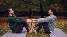 Le ragazze attraenti stanno facendo gli esercizi di yoga nelle paia che si tengono per mano e che mettono i piedi che sollevano i archivi video