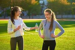 Le ragazze bevono l'acqua un campo degli sport all'aperto di mattina Fotografia Stock
